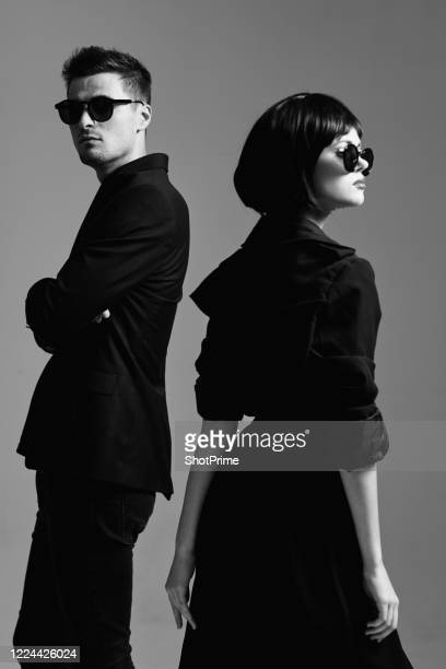 cool and stylish woman and man in black clothes and black sunglasses. - coat stock pictures, royalty-free photos & images