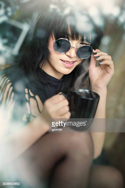 Cool Asian girl with coffee mug smirking through glass window.