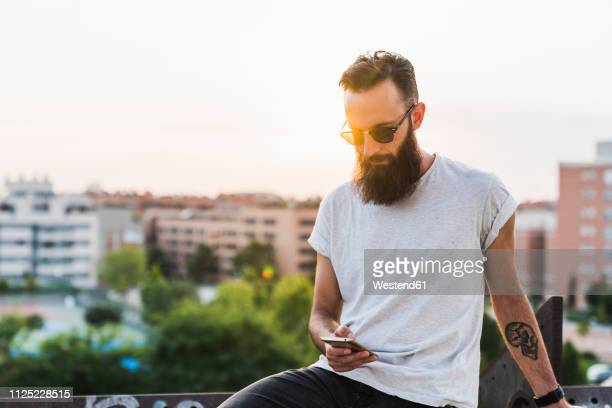 cool bearded young man wearing sunglasses checking cell phone - t shirt imagens e fotografias de stock
