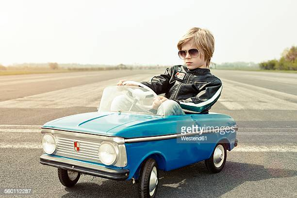 Cool boy in pedal car on race track