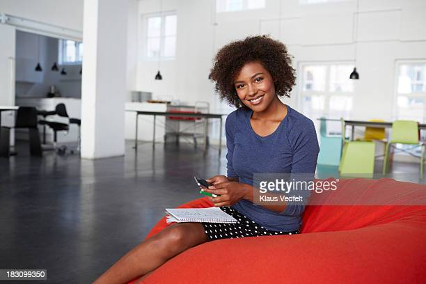 Cool business creative woman holding smartphone