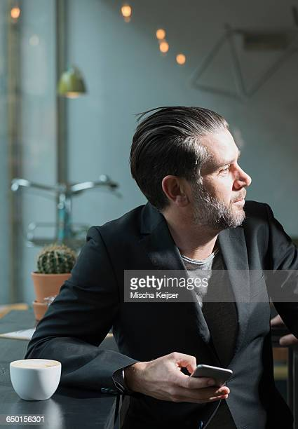 Cool businessman looking over shoulder from cafe window seat