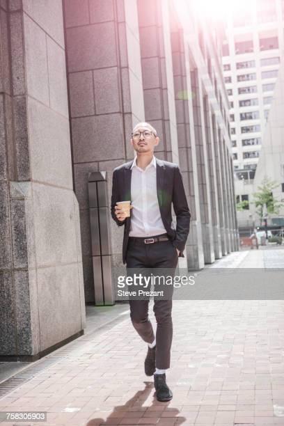 Cool businessman with takeaway coffee strolling along sidewalk, New York, USA