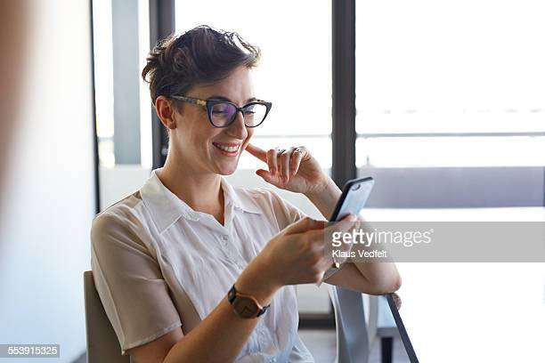 Cool businesswoman looking at phone and laughing