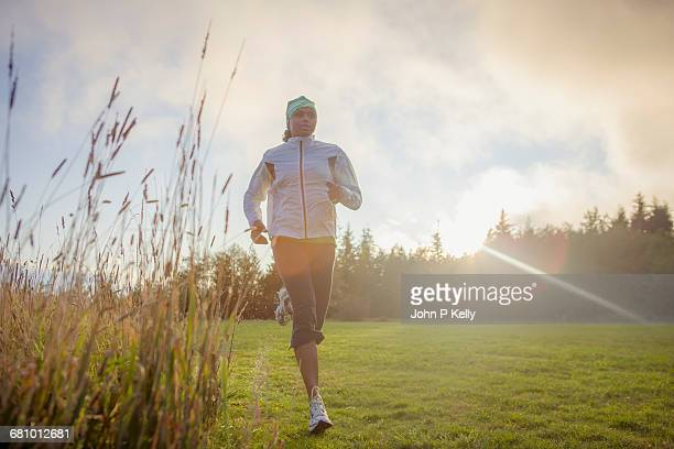 cool early morning run through wet grass - women in wet t shirts stock pictures, royalty-free photos & images