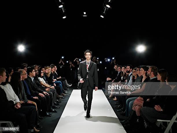 Cool geek walking down runway at fashion show