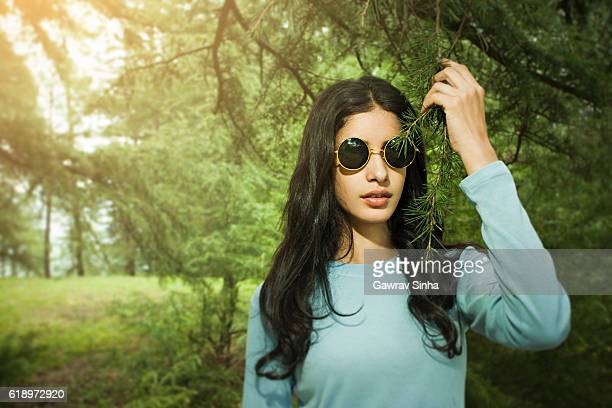 Cool girl in nature holding pine tree branch.