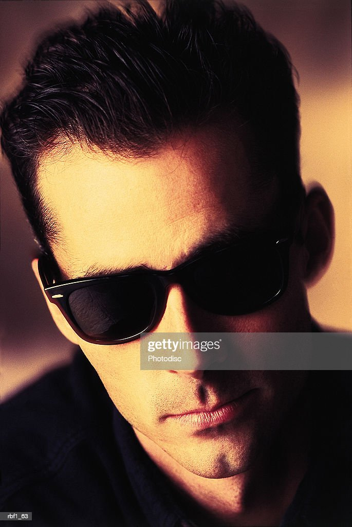 cool guy male man with dark hair and a cleft chin wearing sunglasses and a black shirt has a serious look on his face : Stockfoto