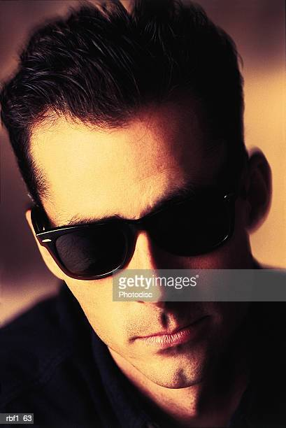 cool guy male man with dark hair and a cleft chin wearing sunglasses and a black shirt has a serious look on his face