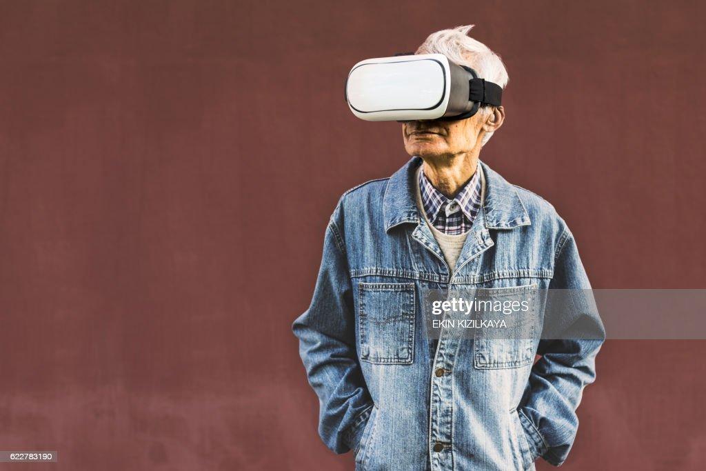 Cool hipster grandpa wearing virtual reality glasses : Stock Photo