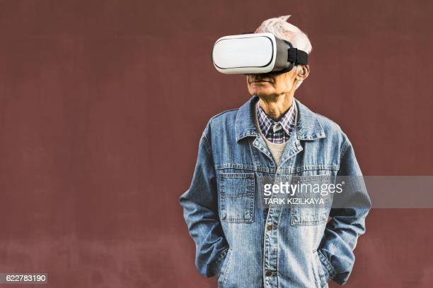 Cool hipster grandpa wearing virtual reality glasses