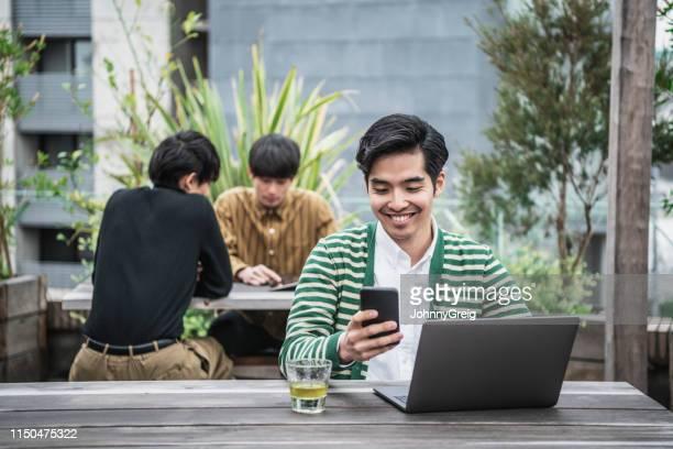 飲み物とノートパソコンや携帯電話を使用してクールな日本のビジネスマン - バーチャルオフィス ストックフォトと画像