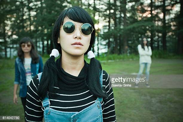 Cool late teen Asian girl wearing sunglasses looking at camera.