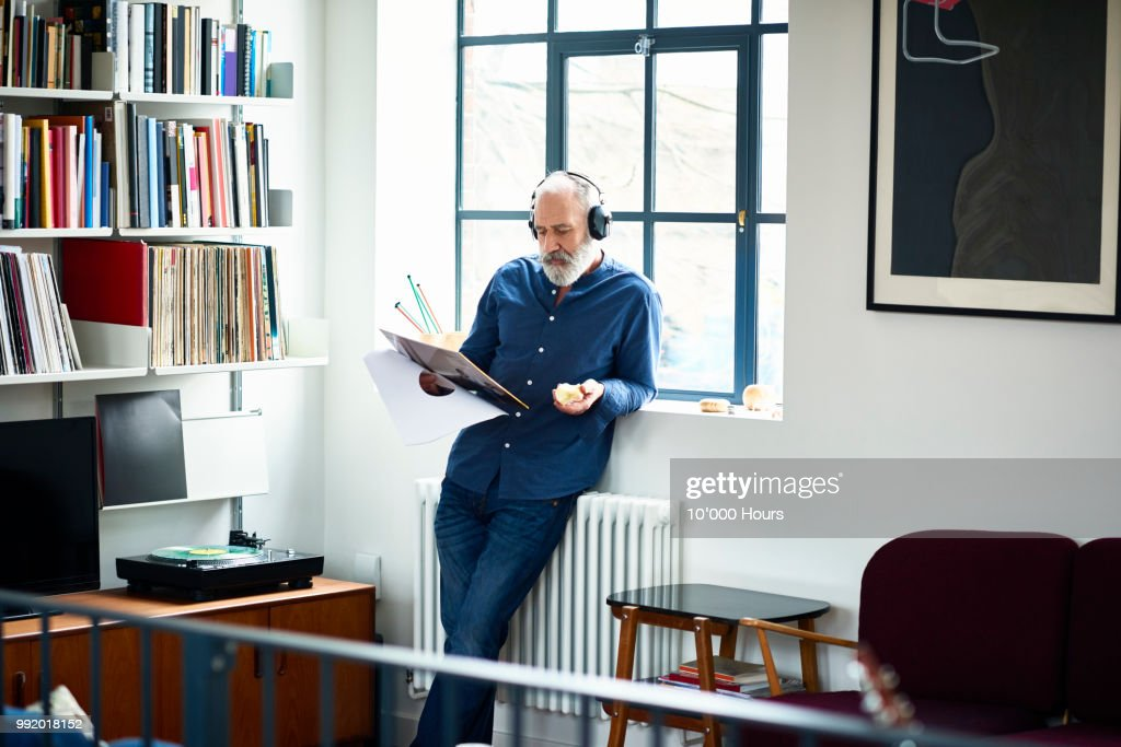 Cool looking senior man in apartment listening to vinyl record : Photo