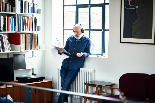 Cool looking senior man in apartment listening to vinyl record - gettyimageskorea