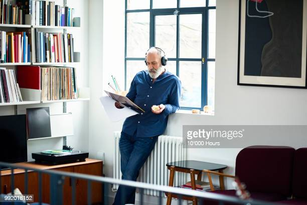 cool looking senior man in apartment listening to vinyl record - freizeit stock-fotos und bilder