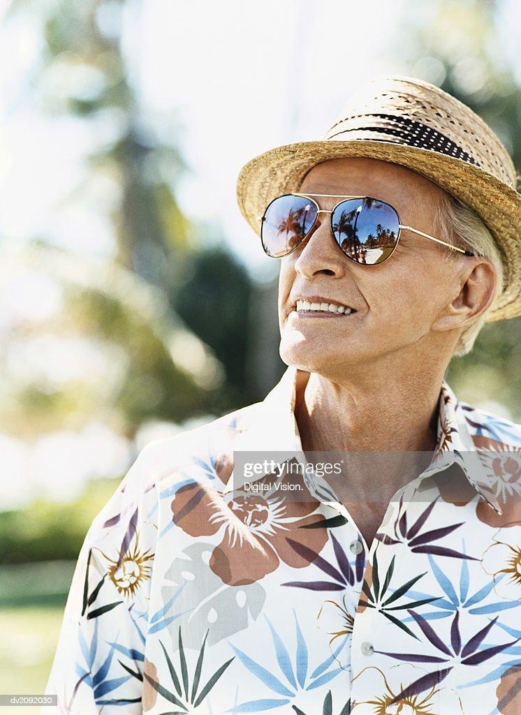 Cool Looking Senior Man Wearing a Hawaiian Shirt and Sunglasses : Stock Photo