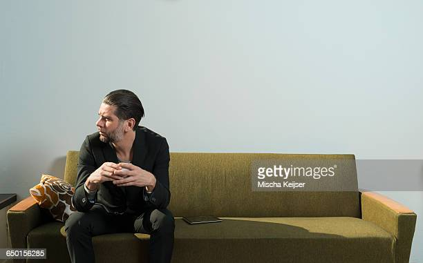 Cool man sitting with cup of coffee on retro cafe sofa