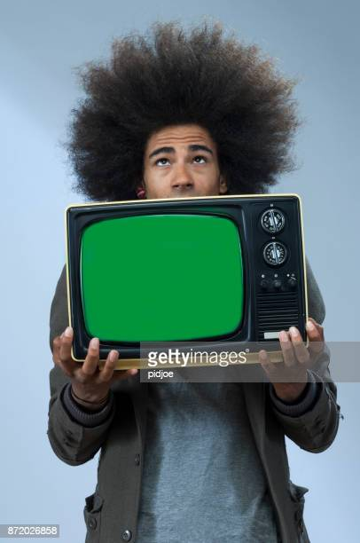 cool man with afro hair and vintage tv, screen chromakey, model looking up. - chroma key imagens e fotografias de stock