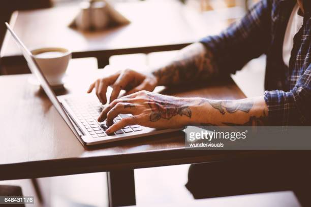 cool man with tatoos typing on laptop in coffee shop - tattoo stock pictures, royalty-free photos & images