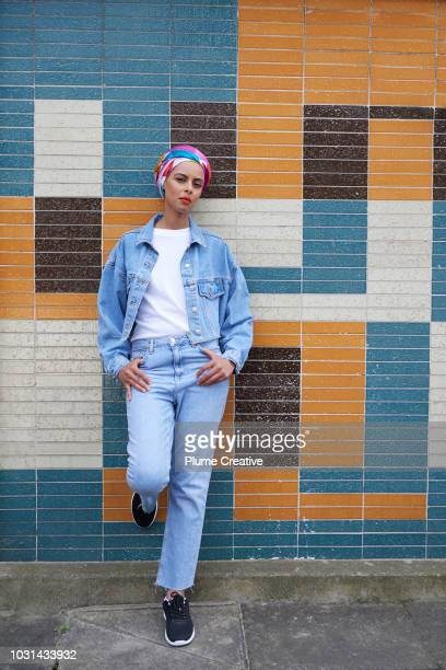 Cool muslim woman leaning on wall looking at camera