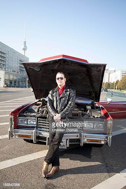 A cool rockabilly guy holding tools leaning against the front of his vintage car, hood up