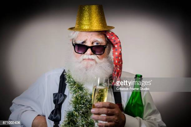 Cool Santa holding a glass and a bottle of champagne on a celebration wearing a gold  party hat
