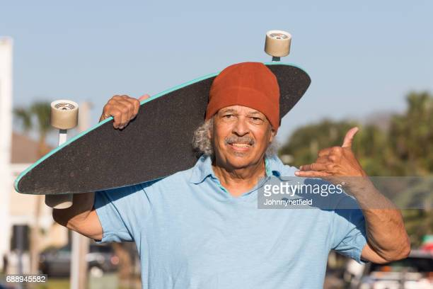 Cool senior hipster posing with a skateboard