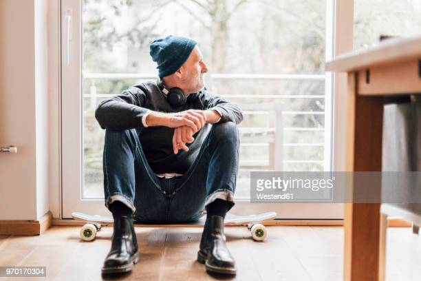 Cool senior man sitting on ground, looking out of window