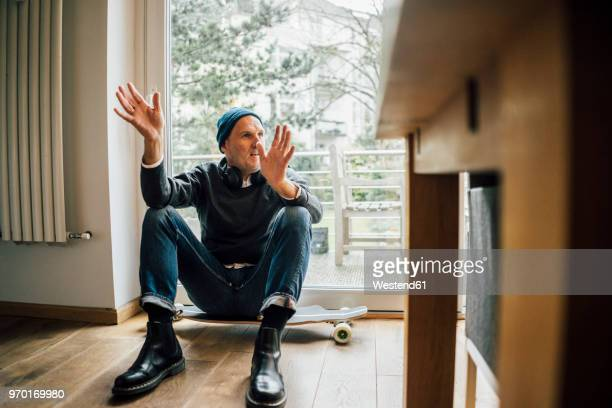 cool senior man sitting on longboard, gesturing and talking - longboard skating stock-fotos und bilder