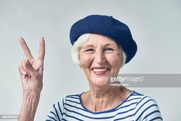 cool senior woman in beret - bella ciao foto e immagini stock