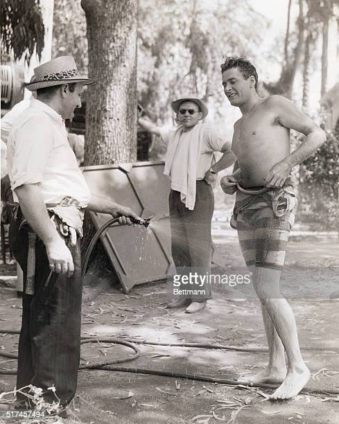 A cool shower helps out on a hot day discovers Errol Flynn who dons this oldfashioned bathing suit for scenes in Warner Brothers Gentleman Jim