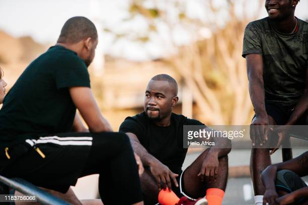 Cool sportsmen sitting around pre-match with one wearing bright orange socks