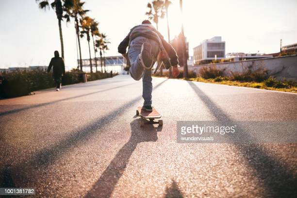 cool teenage boy skateboarding in urban park as a hobby - fast fashion stock pictures, royalty-free photos & images