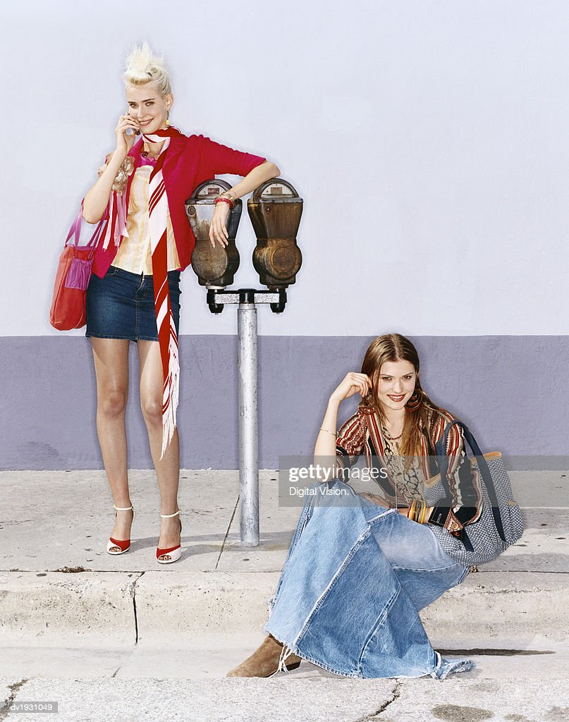 Cool Twentysomething Woman Leaning on a Parking Meter and Another Woman Sitting on the Pavement : Stock Photo