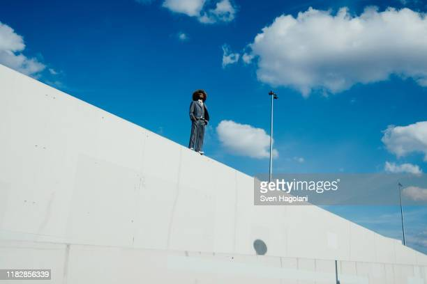 cool, well-dressed young man with afro standing on sunny urban wall - oben stock-fotos und bilder