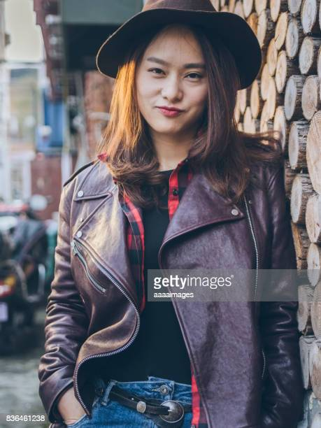 cool woman with floopy hat leaning on decorative wall