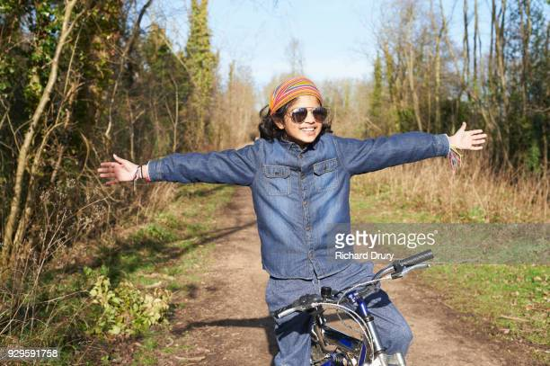 Cool young boy, with arms outstretched, on cycle track