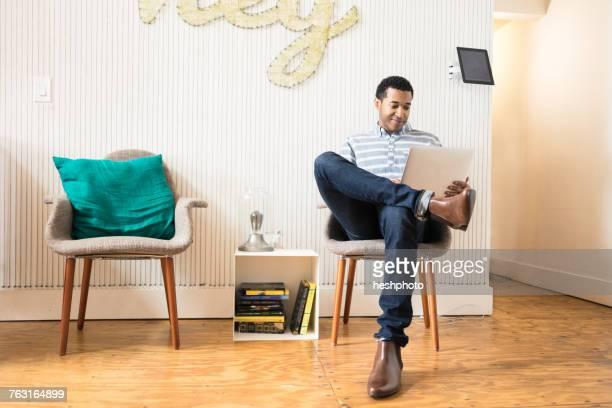 cool young businessman sitting in creative office armchair using laptop - heshphoto stock-fotos und bilder