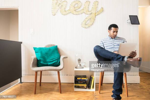 cool young businessman sitting in creative office armchair using laptop - heshphoto stock pictures, royalty-free photos & images