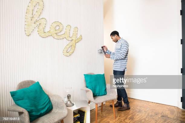 cool young businessman using digital tablet - heshphoto stock-fotos und bilder