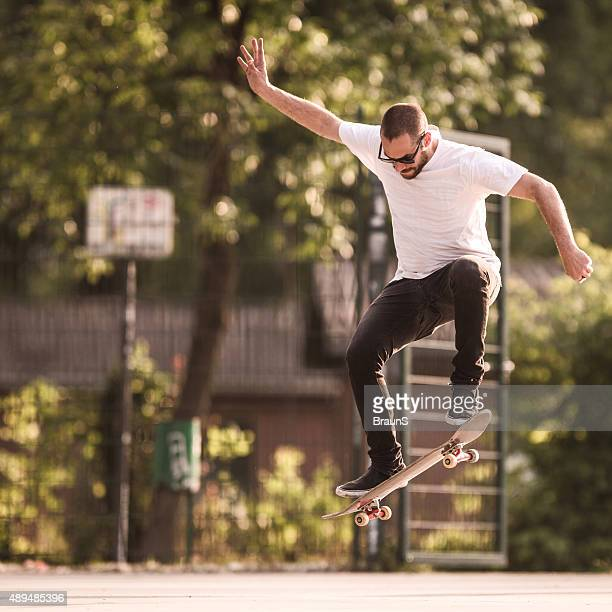 cool young man in ollie position on the street. - ollie pictures stock pictures, royalty-free photos & images
