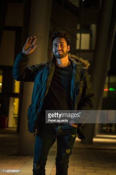 cool young man in the city at night - saluting stock pictures, royalty-free photos & images