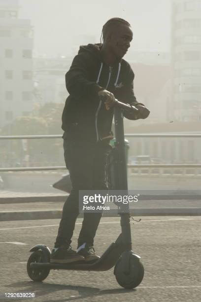 a cool young man riding an electric scooter in the mist - electric scooter stock pictures, royalty-free photos & images