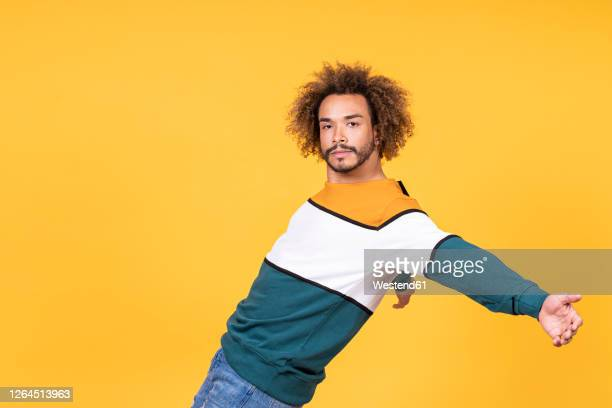 cool young man with curly hair dancing against yellow background - geisteshaltung stock-fotos und bilder