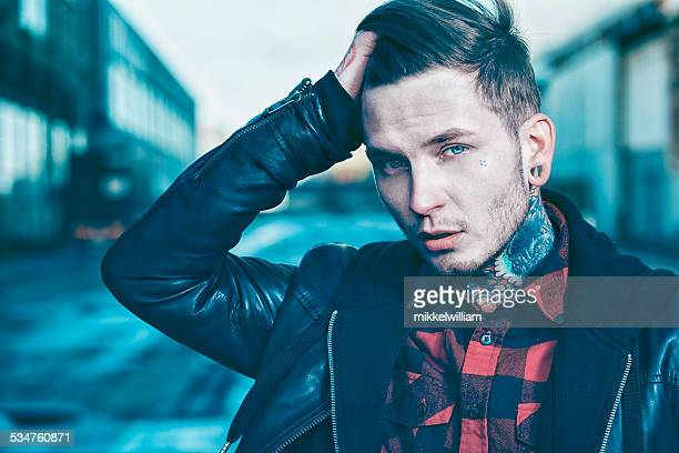 Cool young man with tattoos wears leather jacket
