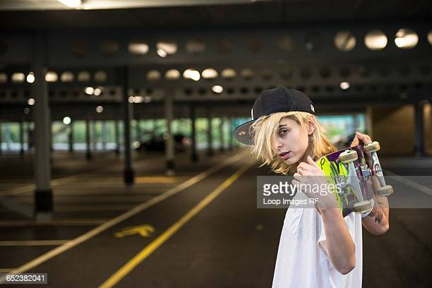 A cool young tattooed skater girl carrying her skateboard over her shoulders