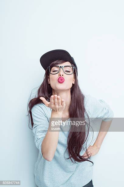 Cool young woman blowing kiss