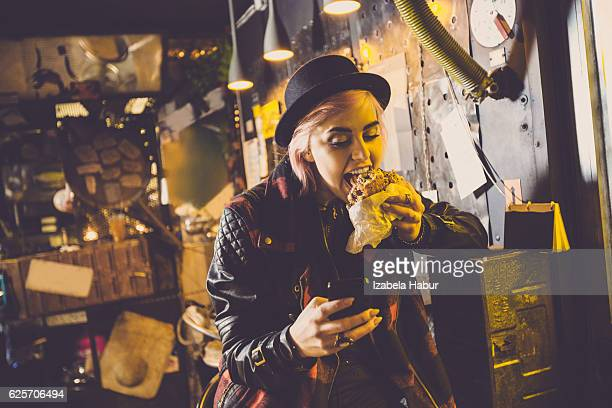 Cool young woman eating burger in pub, using smart phone