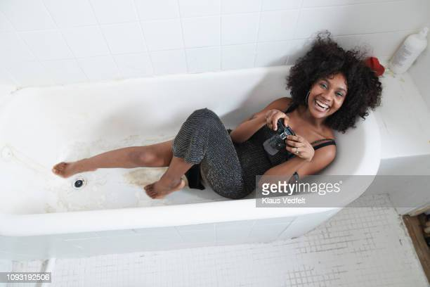 cool young woman laying in bathtub with analog camera - cleaning after party bildbanksfoton och bilder